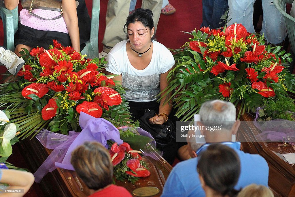 Relatives grieve near the coffins of the victims of the Monteforte Irpino coach crash during the funeral held at a local indoor sports arena on July 30, 2013 in Pozzuoli, Italy. In the second major European transport disaster in a week, 38 people were killed when a coach bus fell from a viaduct near Monteforte Irpino, Italy on July 28.