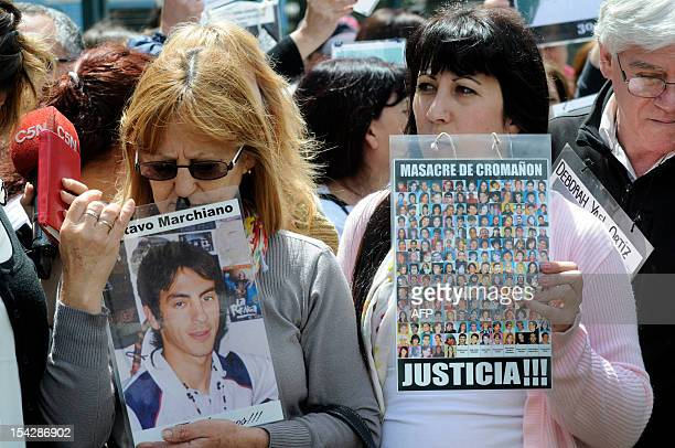Relatives hold pictures of the victims of a fire of 2004 in a nightclub outside the court in Buenos Aires on October 17 on the day the ruling was...