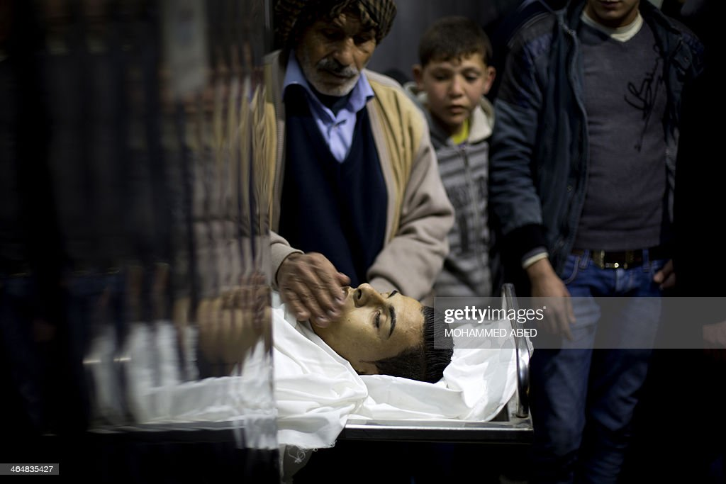 Relatives look at the body of Bilal Samir Oweida, a 20-year-old Palestinian, diplayed at the morgue of Beit Lahia's hospital, northern Gaza Strip on January 24, 2014. Bilal Samir Oweida was 'shot in the chest by Israeli soldiers' east of Jabaliya said Ashraf al-Qudra, a spokesman for the Hamas-run health ministry as Israeli forces said he had entered 'a prohibited area'. AFP PHOTO/MOHAMMED