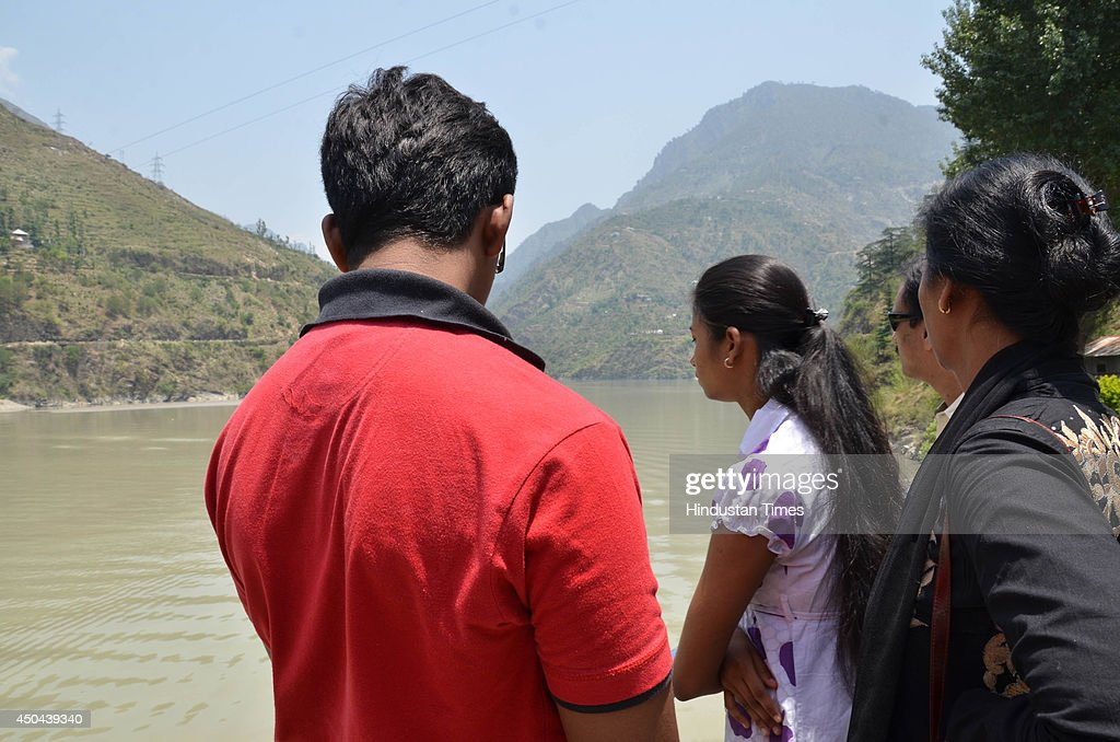 Relatives look at the river as they wait for the body victims of Beas river tragedy on June 11, 2014 in Mandi, India. The rescue team had recovered six bodies so far from the river. A wall of water washed away 24 engineering students and a tour operator Sunday evening after water was released into the river allegedly without a warning from a nearby Pandoh Dam on Beas River.