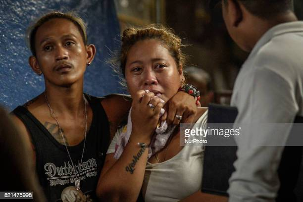 Relatives look on near the scene where a man was killed by unknown assailants in Manila Philippines July 17 2017 The United States congress is the...