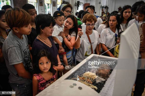 Relatives look over the coffin of Nino Maruso who was killed by police in what they say was a drug buybust operation during his funeral in Caloocan...