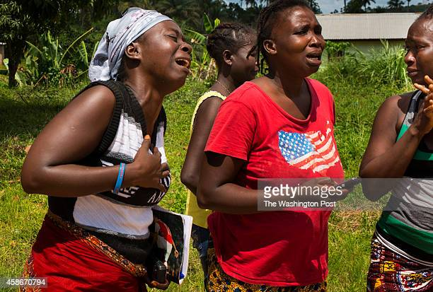 Relatives mourn after the body of Jacqueline Morris is taken away by a Lofa County health department burial team on Friday November 7 2014 in...
