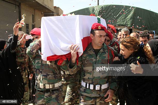 Relatives mourn as Lebanese soldiers carry the coffin of their comrade Mahmoud Ibrahim Hajj Hassan who died in a suicide bombing during his funeral...