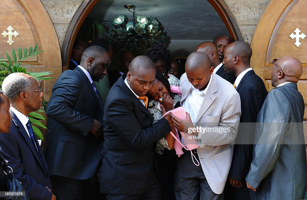 Relatives mourn during the funeral service of Mbugua Mwangi, Kenyan President Uhuru Kenyatta's nephew, and his fiancee Rosemary Wahito in Nairobi on September 27, 2013 after they were both killed in the Westagte Mall attacks. Kenyan and foreign forensics teams scoured the wreckage of a Nairobi shopping mall for bodies and clues after a four-day siege by Islamist gunmen left 67 dead and dozens more missing. AFP PHOTO/JOHN MUCHACHA