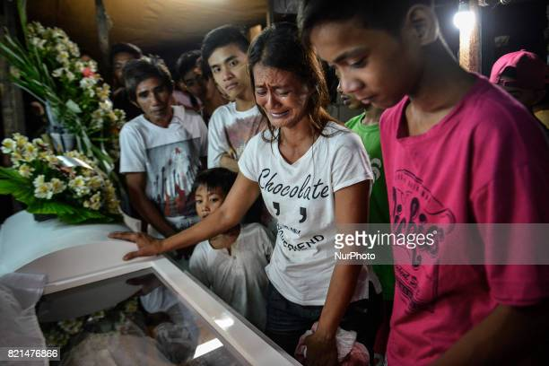 Relatives mourn during the funeral wake of Marvin De Los Santos who was killed by unknown assailants in Quezon city Metro Manila Philippines July 20...