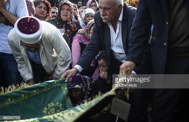 Relatives mourn near the grave of a victim of the twin bombings in Ankara during the funeral in Istanbul on October 12 2015 Turkey woke in mourning...