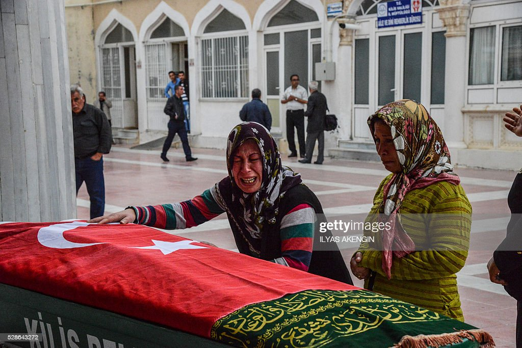 Relatives mourn next to a coffin on May 6, 2016 in Kilis, during the funeral ceremony of 5 years old Nisa Done Sezer who was killed the day before after a rocket hit the house. One person was killed and seven more wounded when rockets fired from Syria slammed into the Turkish border region of Kilis, which has been regularly targeted by jihadists this year, the Dogan news agency said. / AFP / ILYAS