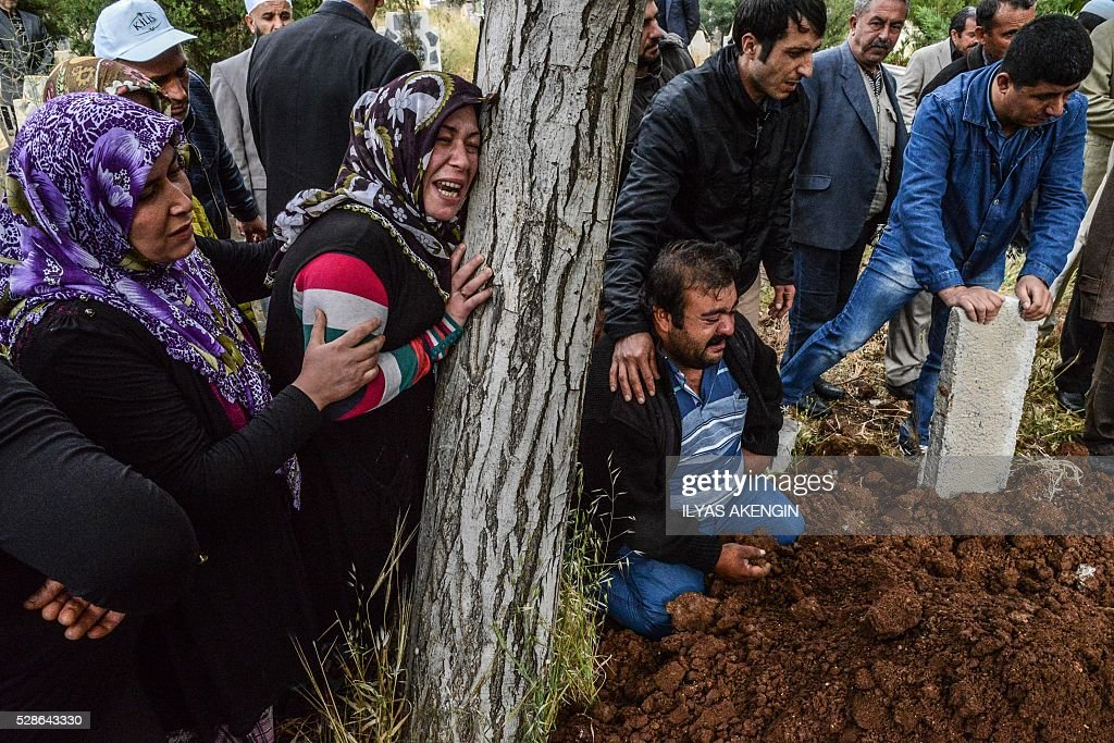 Relatives mourn next to a grave on May 6, 2016 in Kilis, during the funeral ceremony of 5 years old Nisa Done Sezer who was killed the day before after a rocket hit the house. One person was killed and seven more wounded when rockets fired from Syria slammed into the Turkish border region of Kilis, which has been regularly targeted by jihadists this year, the Dogan news agency said. / AFP / ILYAS