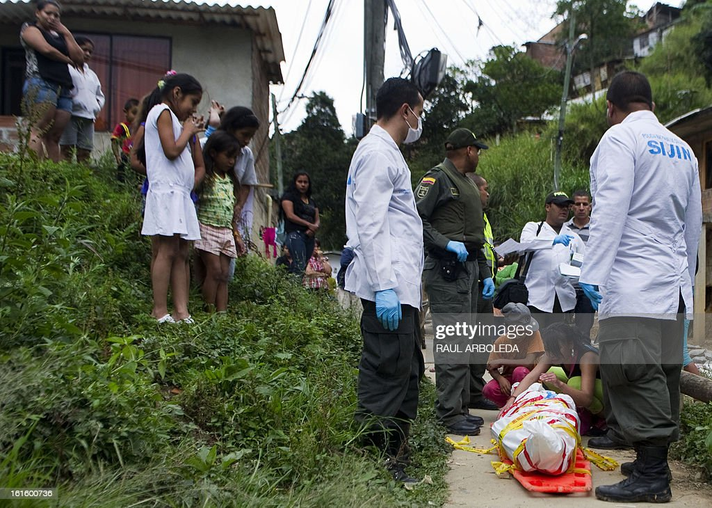 Relatives mourn next to the body of a man killed at the Commune 13 -- one of the shantytowns with the highest rates of urban violence and displacement-- in Medellin, Antioquia department, Colombia, on February 12, 2013. So far this year, more than 105 people have been killed by urban conflict due to disputes between gangs for the control of the territory. Violent street gangs have 'invisible borders' that delineate their territories in Medellin, ranked the 14th most dangerous city in the world. AFP PHOTO/Raul ARBOLEDA