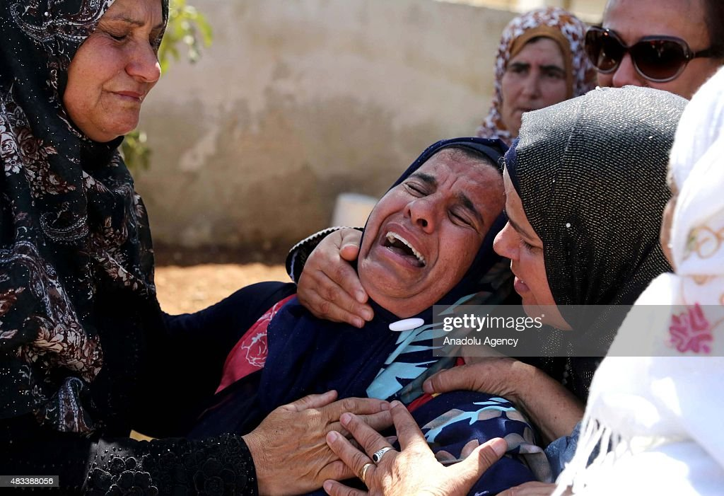 Relatives mourn on August 8 2015 in Duma village of West Bank's city of Nablus during the funeral ceremony of Saad Dawabsheh the father of a...