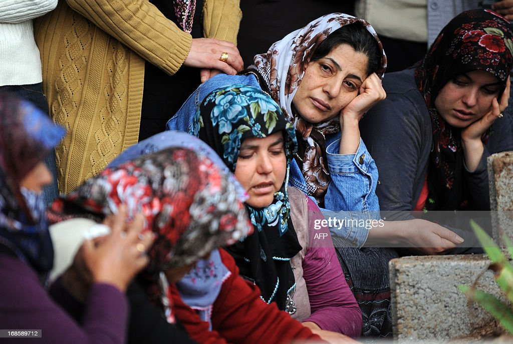 Relatives mourn on May 12, 2013 at the grave of a victim of a car bomb which went off on May 11 at Reyhanli in Hatay just a few kilometres from the main border crossing into Syria. Turkey was reeling from twin car bomb attacks which left at least 43 people dead in a town near the Syrian border, with Ankara blaming pro-Damascus groups and vowing to bring the perpetrators to justice. A Syrian minister denied on May 12 accusations that Damascus was behind a bomb attack in a Turkish town that left dozens dead, a day after Ankara blamed supporters of President Bashar al-Assad for the blasts.