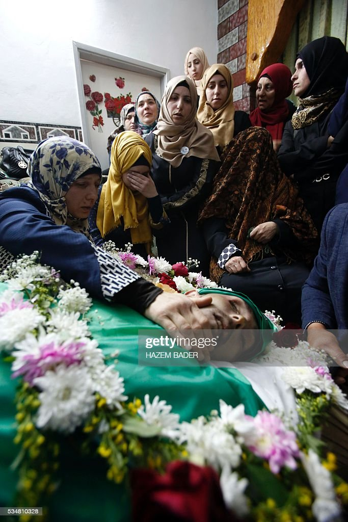 The mother (L) of Abdul Fatah al-Sharif, a wounded Palestinian assailant who was shot dead by an Israeli soldier after laying prone on the ground in the city of Hebron on March 24, mourns during his funeral on May 28, 2016, in the West Bank city of Hebron. An Israeli soldier caught on video shooting a wounded Palestinian assailant in the head was charged with manslaughter in a case that has sparked widespread controversy. Prosecutors presented the indictment to a military court over the March 24 killing, which occurred minutes after the Palestinian had stabbed another soldier and lay prone on the ground wounded by gunfire, according to Israeli authorities. / AFP / HAZEM