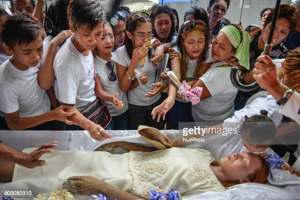 Relatives mourn over the body of Leah Espiritu who relatives say was a drug runner during her funeral in Caloocan north of Manila Philippines June 11...