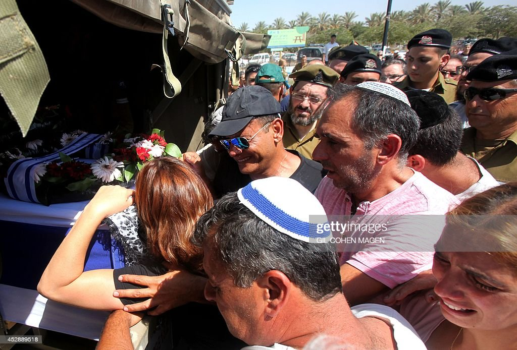 Relatives mourn over the coffin of Israeli soldier Corporal Meidan Maymon Biton during his funeral at the cemetery of the southern Israeli city of...