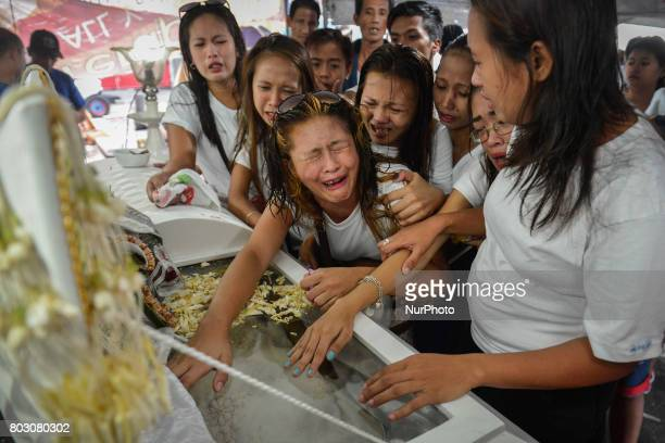 Relatives mourn over the coffin of Leah Espiritu who relatives say was a drug runner during her funeral in Caloocan north of Manila Philippines June...