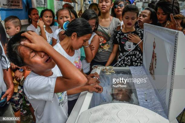 Relatives mourn over the coffin of sixteen year old Arjay Suldao who was killed by unknown men after being missing for days during his funeral in...
