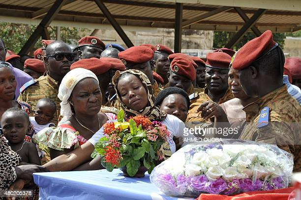 Relatives mourn over the coffins of six Burkinese peacekeepers who were killed in an ambush in northern Mali upon the repatriation of the bodies to...