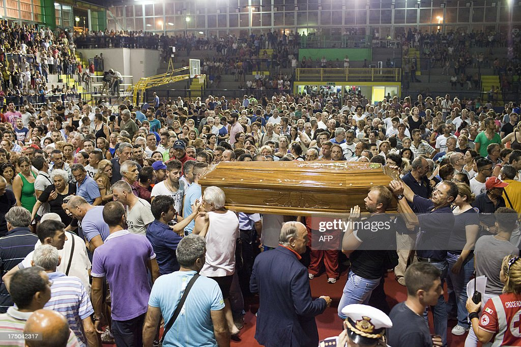 Relatives mourn victims of a bus crash on July 29, 2013 in a sport hall in Pozzuoli. An Italy in mourning prepared to hold a mass funeral for 38 people killed when a coach plunged off a viaduct near Naples in the worst such accident in western Europe in the last decade. Hundreds of relatives who had spent agonising hours on Monday identifying the victims before they were carried off in flower-covered coffins were expected to attend the funeral in a vast sports hall near the town of Pozzuoli.