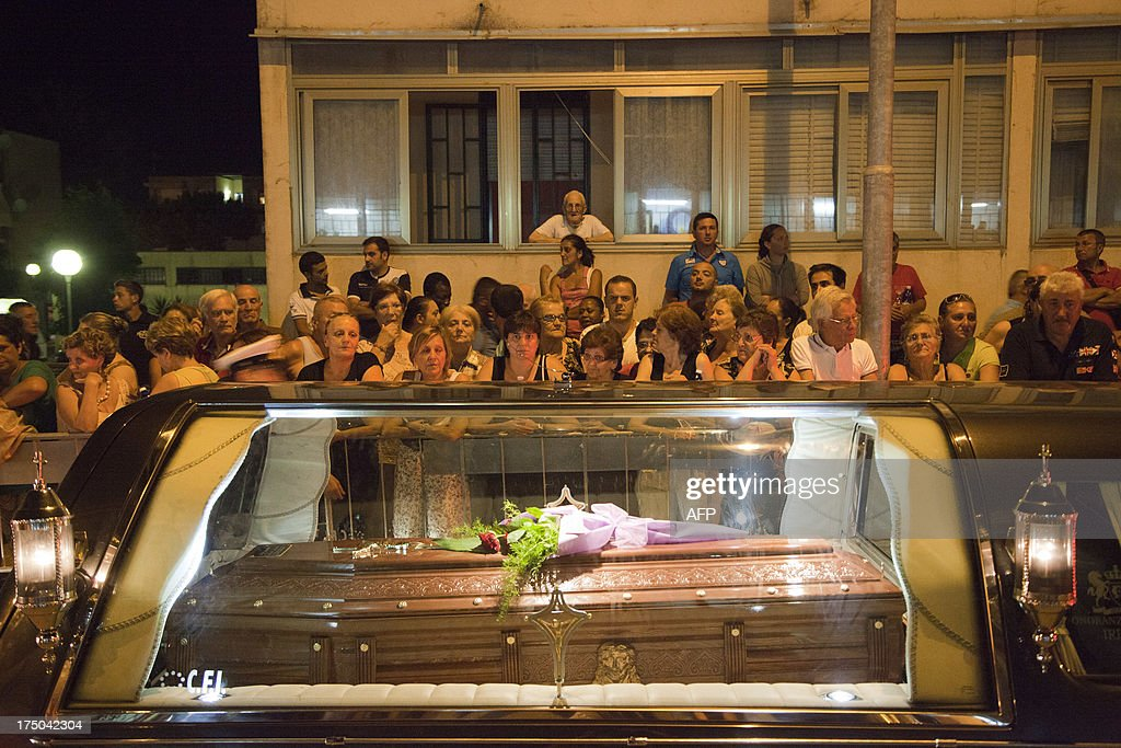 Relatives mourn victims of a bus crash on July 29, 2013 in Monteforte Irpino. An Italy in mourning prepared to hold a mass funeral for 38 people killed when a coach plunged off a viaduct near Naples in the worst such accident in western Europe in the last decade. Hundreds of relatives who had spent agonising hours on Monday identifying the victims before they were carried off in flower-covered coffins were expected to attend the funeral in a vast sports hall near the town of Pozzuoli.