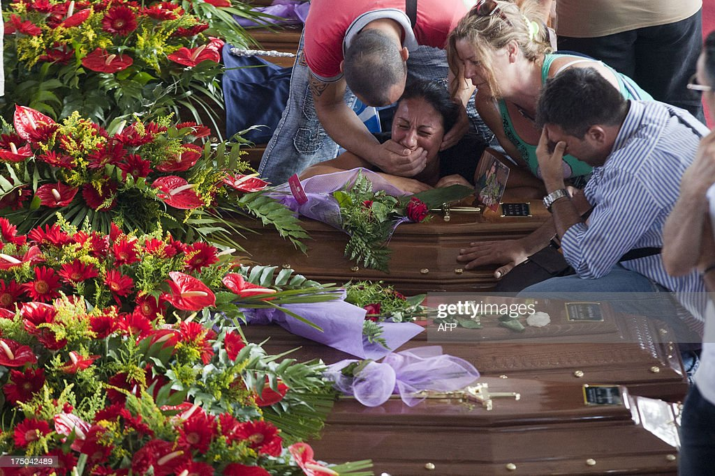 Relatives mourn victims of a bus crash on July 30, 2013, in Moterusciello, southern Italy, during a mass funeral for the 38 people killed in Italy when a coach plunged off a viaduct near Naples. The coach, carrying 48 people including children, rammed several cars after failing to break on a bend, smashing through a crash barrier and off the viaduct to plunge 30 metres (98 feet) down. Prosecutors have launched an investigation into possible manslaughter over the accident, the worst such crash in western Europe in the last decade.