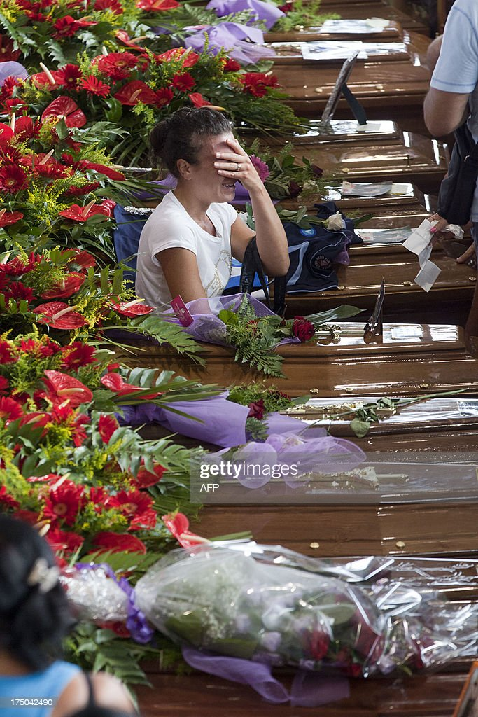 Relatives mourn victims of a bus crash on July 30, 2013, in Moterusciello, southern Italy, during a mass funeral for the 38 people killed in Italy when a coach plunged off a viaduct near Naples. The coach, carrying 48 people including children, rammed several cars after failing to break on a bend, smashing through a crash barrier and off the viaduct to plunge 30 metres (98 feet) down. Prosecutors have launched an investigation into possible manslaughter over the accident, the worst such crash in western Europe in the last decade. AFP PHOTO / CARLO HERMANN