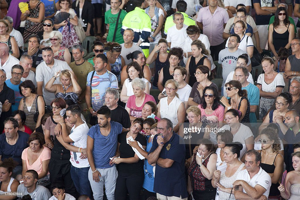 Relatives mourn victims on July 30, 2013, in Moterusciello, southern Italy, during a mass funeral for the 38 people killed in Italy when a coach plunged off a viaduct near Naples. The coach, carrying 48 people including children, rammed several cars after failing to break on a bend, smashing through a crash barrier and off the viaduct to plunge 30 metres (98 feet) down. Prosecutors have launched an investigation into possible manslaughter over the accident, the worst such crash in western Europe in the last decade.