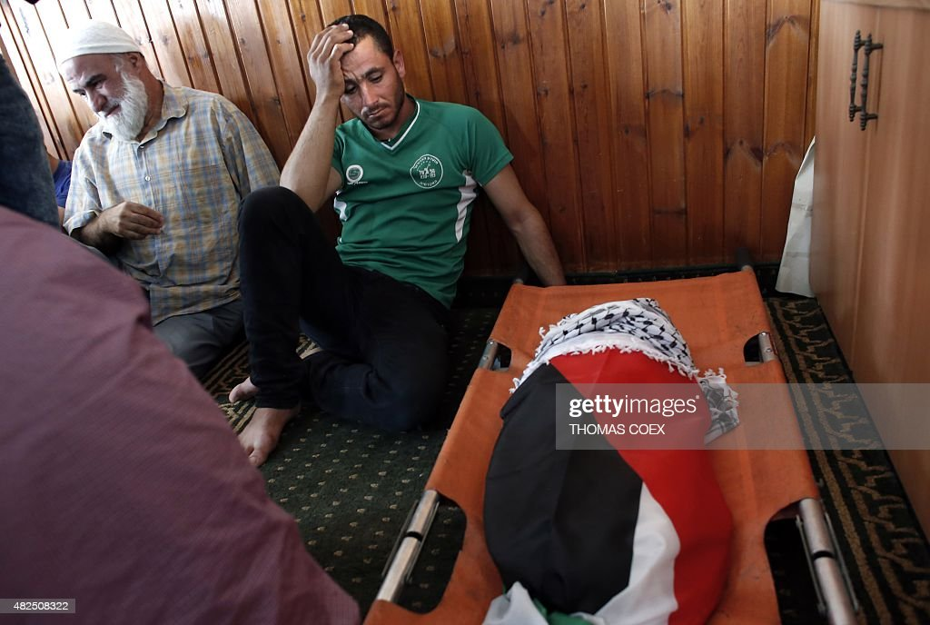 Relatives of 18monthold Palestinian toddler Ali Saad Dawabsha who died after his house was set on fire by Jewish settlers mourn next to his body...