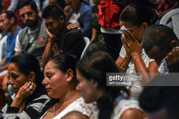 Relatives of 21 victims of the Colombian civil war mourn during a ceremony in which they wake the remains of their loved ones recently found in...