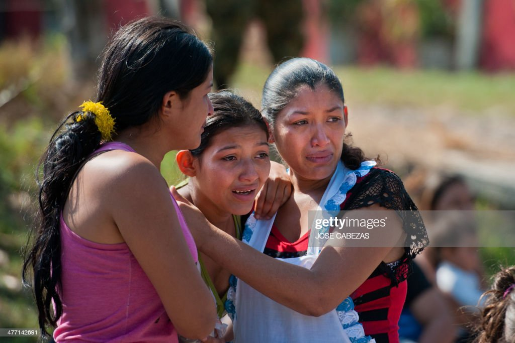 Relatives of a gang member who was killed, gestures as police forensics work on the murder scene in the town of Nejapa, 24 km north from San Salvador, El Salvador on March 7, 2014 prior to the second round of the presidential elections to be held on March 9. AFP PHOTO/ Jose CABEZAS