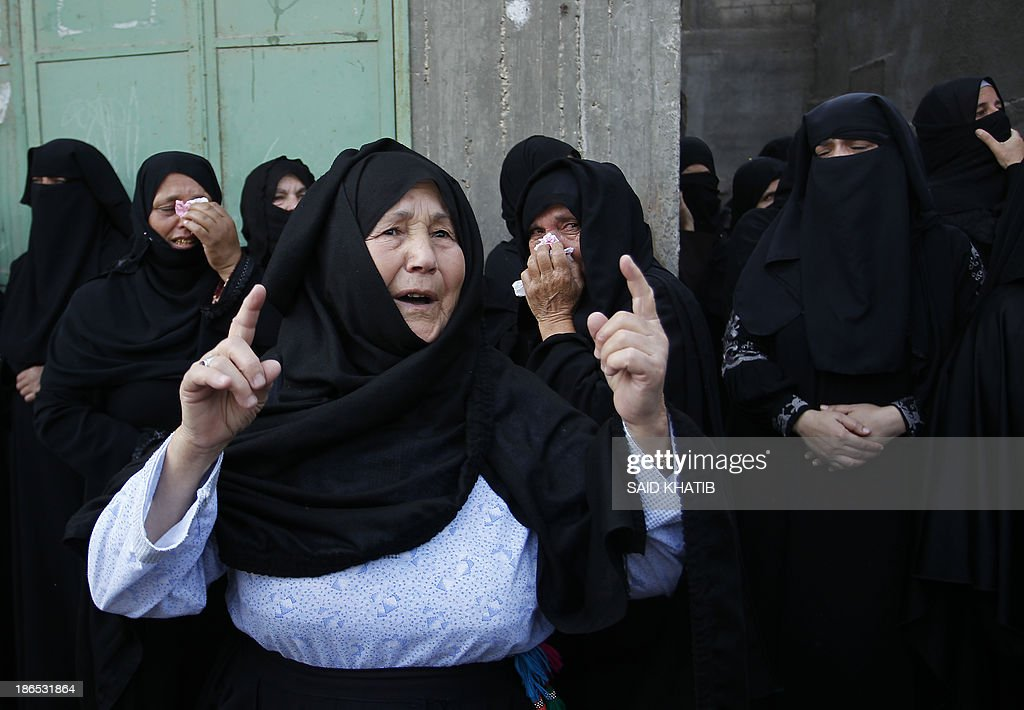 Relatives of a local commander of Hamas's military wing Rabieh Barikeh, one of the four Hamas militants killed overnight in a firefight with Israeli troops, mourn during his funeral on November 1, 2013 in Khan Yunis in the southern Gaza Strip. Barikeh was killed by tank fire, Palestinian officials said, while the Israeli army said five of its soldiers were wounded by an explosive device. The Israeli military said the fighting erupted when an explosive device went off as troops were clearing a tunnel from the Gaza Strip into Israel, allegedly to be used as a springboard for militant attacks.