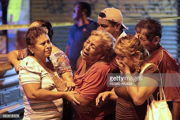 Relatives of a man murdered on a street cry in the tourist city of Acapulco Guerrero State Mexico on October 1 2015 Acapulco once known as a...