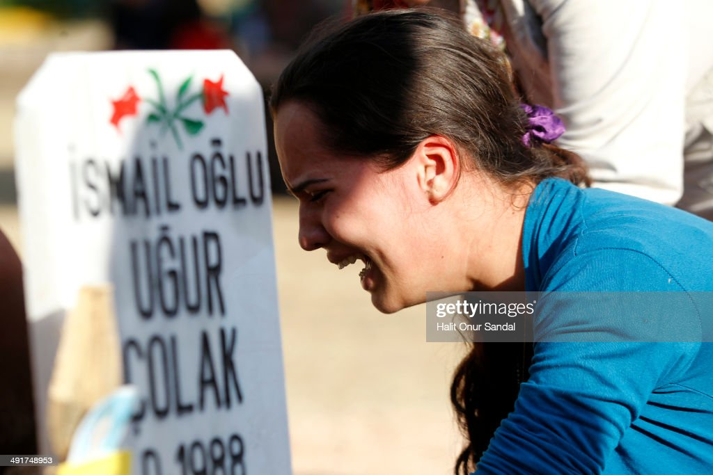 Relatives of a miner mourn beside his grave following the Soma mining disaster on May 17 2014 in Soma Manisa Turkey Manisa Governorate has banned all...