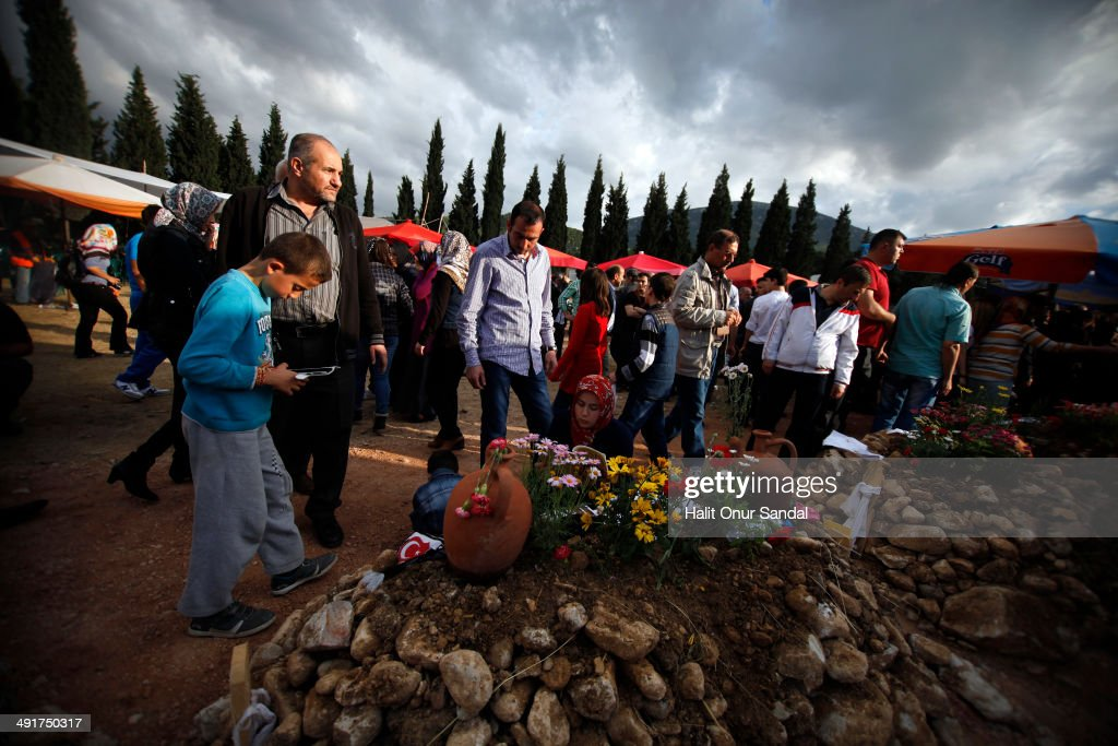 Relatives of a miner read holy Kuran beside his grave following the Soma mining disaster on May 17 2014 in Soma Manisa Turkey Manisa Governorate has...