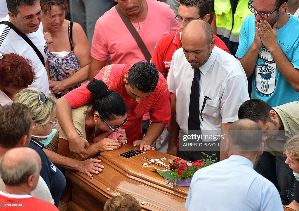 Relatives of a victim of a bus crash on the road between Monteforte Irpino and Baiano mourn over a coffin on July 29, 2013, near the morgue in Monteforte Irpino, southern Italy. A coach carrying pilgrims plunged off a motorway flyover near Naples in southern Italy, killing at least 39 people in one of the worst such accidents in Europe in recent years.
