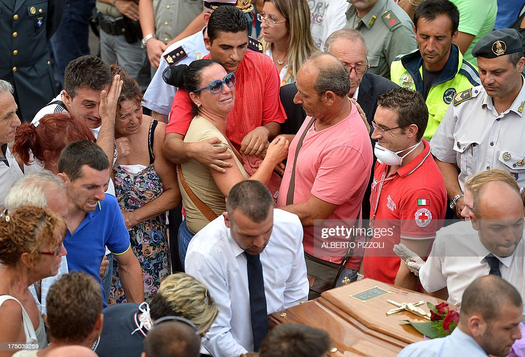 Relatives of a victim of a bus crash on the road between Monteforte Irpino and Baiano mourn on July 29, 2013, near the morgue in Monteforte Irpino, southern Italy. A coach carrying pilgrims plunged off a motorway flyover near Naples in southern Italy, killing at least 39 people in one of the worst such accidents in Europe in recent years. AFP PHOTO / ALBERTO PIZZOLI