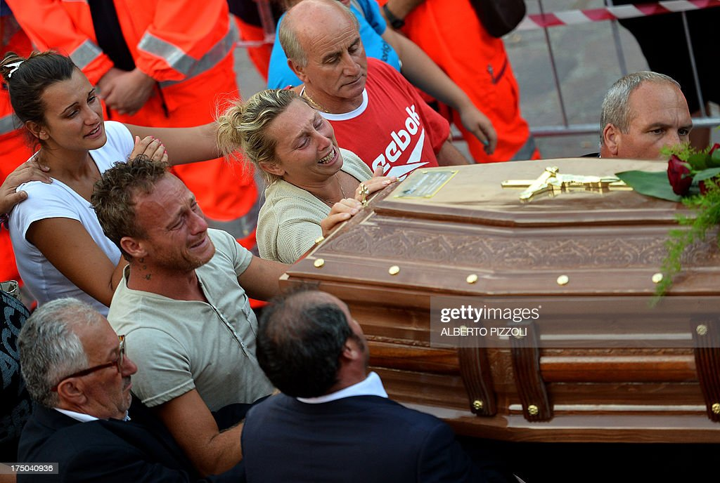 Relatives of a victim of a bus crash on the road between Monteforte Irpino and Baiano mourn over a coffin on July 29, 2013, near the morgue in Monteforte Irpino, southern Italy. A coach carrying pilgrims plunged off a motorway flyover near Naples in southern Italy, killing at least 39 people in one of the worst such accidents in Europe in recent years. AFP PHOTO / ALBERTO PIZZOLI