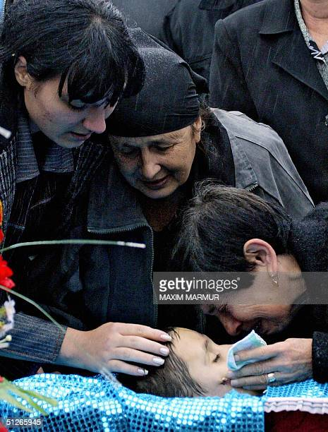 Relatives of a victim of the Russian hostage siege mourn over his coffin at the cenetery in Beslan North Ossetia 06 September 2004 Dozens of coffins...