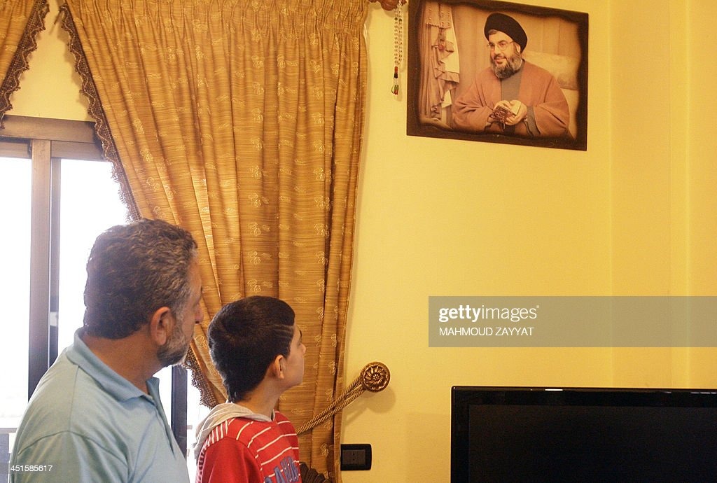 Relatives of Adnan Mussa al-Mohammad, one of the suspects responsible for the twin attack on the Iranian embassy in Beirut earlier this week, looks at a portrait of Hassan Nasrallah, the head of Lebanon's militant Shiite Muslim movement Hezbollah on November 23, 2013 at the family home, in the Lebanese southern village of Beissariyeh. The Lebanese army confirmed that DNA testing showed the second bomber was Adnan Mussa al-Mohammad, a Palestinian who reportedly supported Sheikh Ahmed Assir, a radical Sunni preacher on the run since his supporters clashed with Lebanese troops in the summer, killing 17 soldiers.
