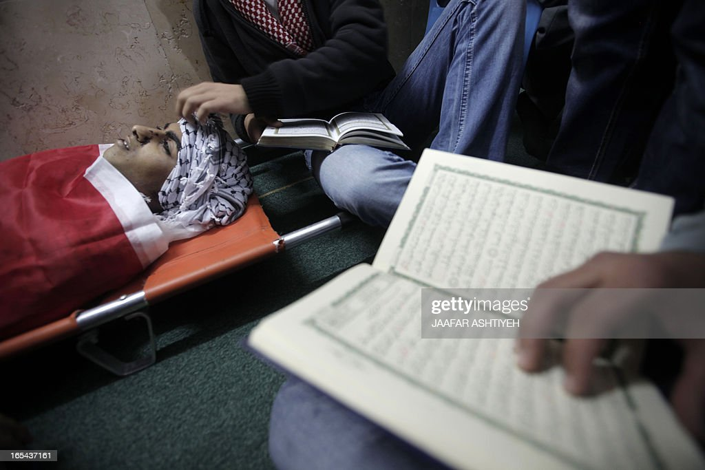 Relatives of Amer Nasser, a 17-year-old Palestinian shot by Israeli troops, pray over his body during his funeral at a mosque in the West Bank town of Anabta near Tulkarem on April 4, 2013. The West Bank simmered with anger as thousands joined the funeral of prisoner Maisara Abu Hamdiyeh who died in an Israeli jail and similar numbers gathered to bury two teens shot dead overnight during clashes over the death of the prisoner, Israeli and Palestinian sources said.