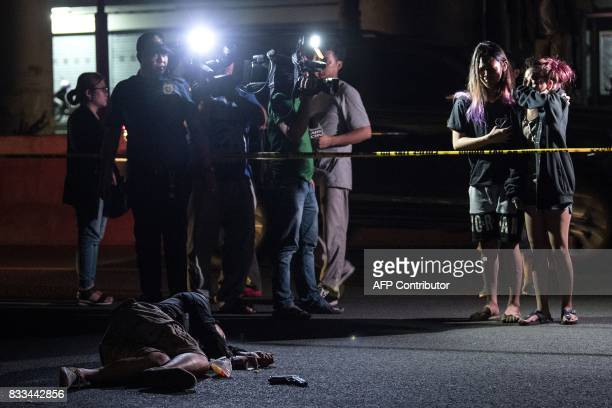 Relatives of an alleged drug dealer killed during a police antidrug operation react upon seeing his body in Manila on August 17 2017 Police in the...