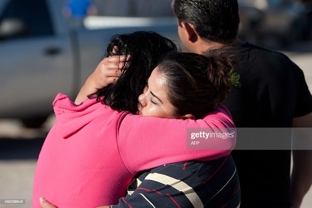 Relatives of eight members of a family killed by gunmen mourn in Ciudad Juarez Mexico on November 17 2013 AFP PHOTO/JESUS ALCAZAR