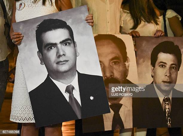 Relatives of former deputies kidnapped and killed by the FARC in 2007 hold their pictures during a private ceremony where FARC leaders acknowledged...