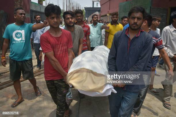 Relatives of Indian bus crash victim Santosh Kumari carry her body to a funeral pyre in Amritsar on June 16 a day after ten pilgrims were killed and...