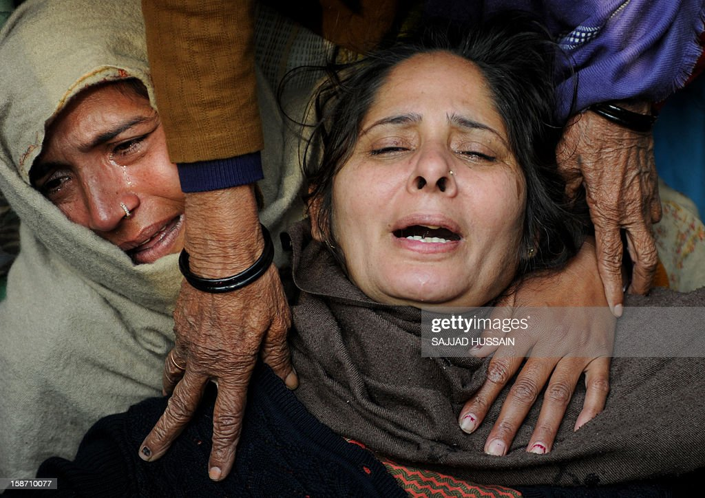 Relatives of Indian policeman Subash Tomar mourn during his funeral in New Delhi on December 25, 2012. Tomar, a 47-year-old constable Indian policeman who was injured in clashes during a protest over a gang-rape in New Delhi has died. Tomar, a 47-year-old constable deployed at the India Gate monument on December 23 to control the protests, was beaten up by a mob and rushed to hospital by the police. AFP PHOTO/SAJJAD HUSSAIN