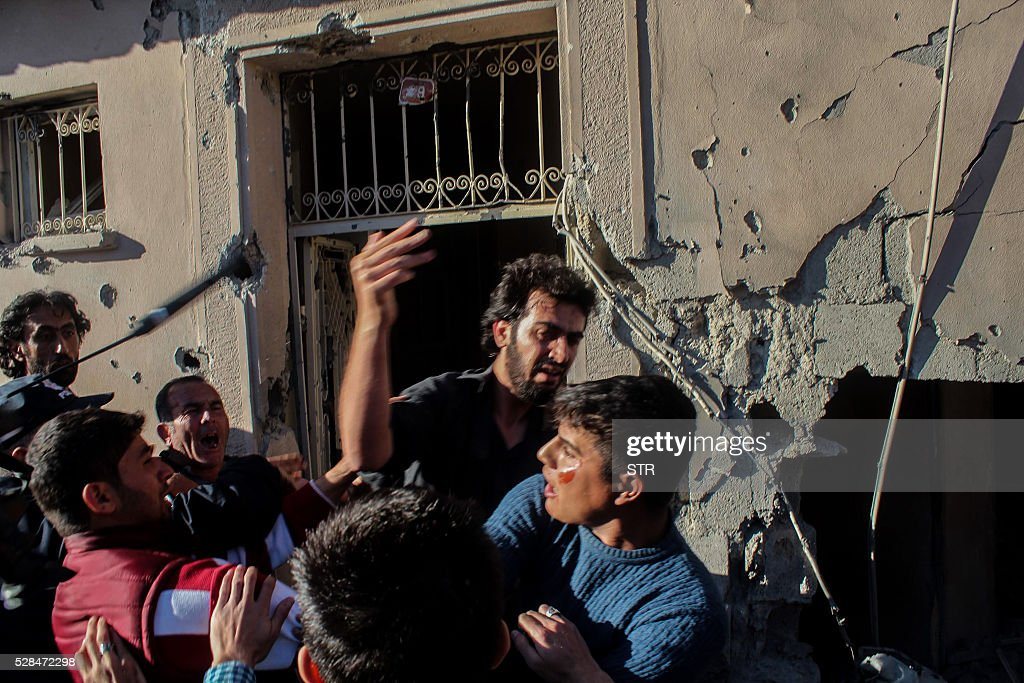 Relatives of injured people react at the site after a rocket hit a house on May 5, 2016 in Kilis. One person was killed and seven more wounded when rockets fired from Syria slammed into the Turkish border region of Kilis, which has been regularly targeted by jihadists this year, the Dogan news agency said. / AFP / STR