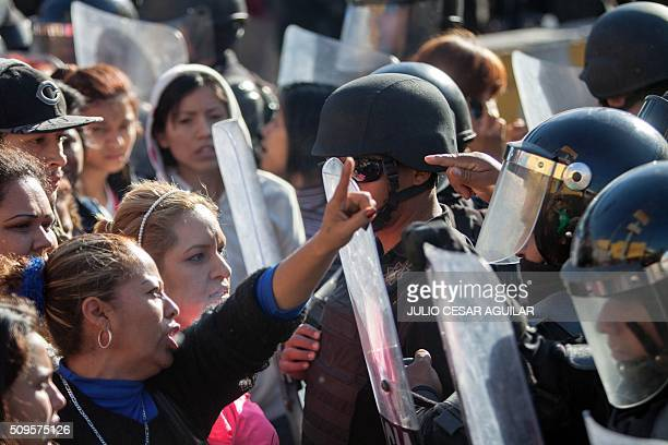 Relatives of inmates argue with the riot police as they gather outside the Topo Chico prison in the northern city of Monterrey in Mexico where...