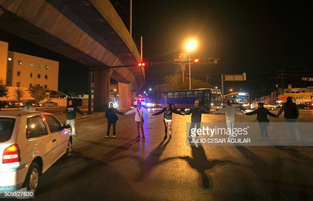 Relatives of inmates block a road outside the Topo Chico prison in the northern city of Monterrey in Mexico where according to local media at least...