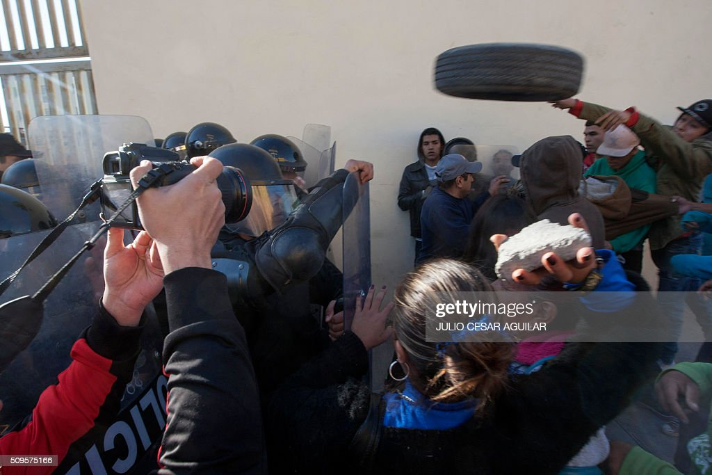 Relatives of inmates throw objects at riot police officers as they gather outside the Topo Chico prison in the northern city of Monterrey in Mexico where according to local media at least 30 people died in a prison riot on February 11, 2016. Riot police and ambulances were deployed at the Topo Chico prison as smoke billowed from the facility. Broadcaster Televisa reported that 30 died while Milenio television spoke of 50 victims, with inmates and prison guards among them. AFP PHOTO / JULIO CESAR AGUILAR / AFP / Julio Cesar Aguilar