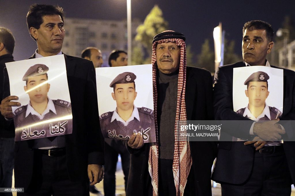 Relatives of Jordanian air force pilot Maaz alKassasbeh who crashed in Syria with a F16 last month carry posters with his portrait and a slogan...